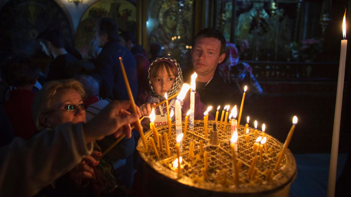 Visitors light candles in the Church of the Nativity, the site revered by Christians as Jesus' birthplace, ahead of Christmas in the West Bank town of Bethlehem. (Reuters)