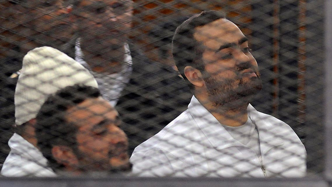 Political activists Ahmed Maher (in white hat), Ahmed Douma (L) and Mohamed Adel (R) of the 6 April movement look on from behind bars in Abdeen court in Cairo, December 22, 2013.