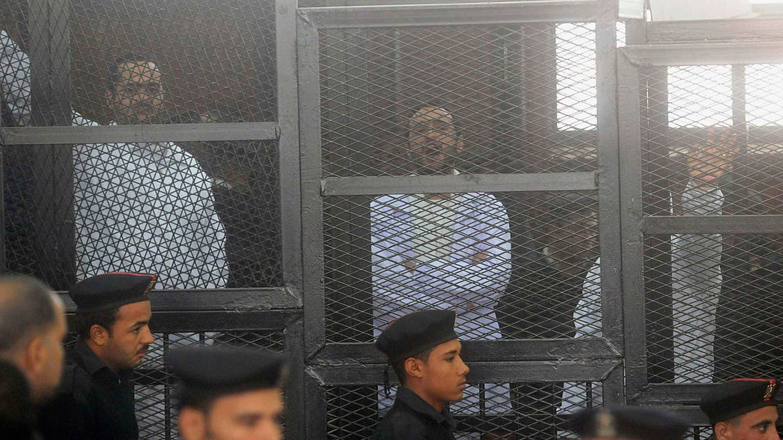 Political activists Ahmed Maher (R), Ahmed Douma (C) and Mohamed Adel, founder of 6 April movement, look on from behind bars in Abdeen court in Cairo, December 22, 2013. Reuters