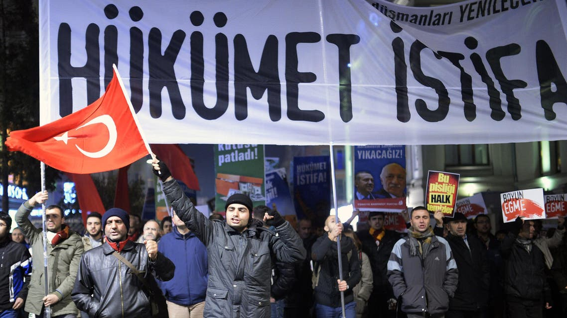 """A demonstrator waves a Turkish flag as others hold a banner reading """"government resign"""" during a protest against corruption in the Kadikoy district of Istanbul on December 25, 2013. Reuters"""