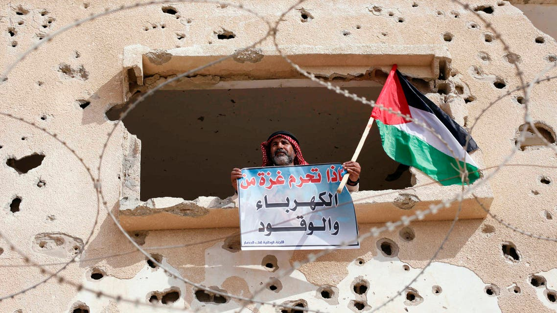 """A Palestinian man holds a Palestinian flag and a sign that reads, """"Why is Gaza deprived of electricity and fuel?"""" during a rally calling on the Egyptian authorities to open the Rafah crossing in November. (File photo: Reuters)"""