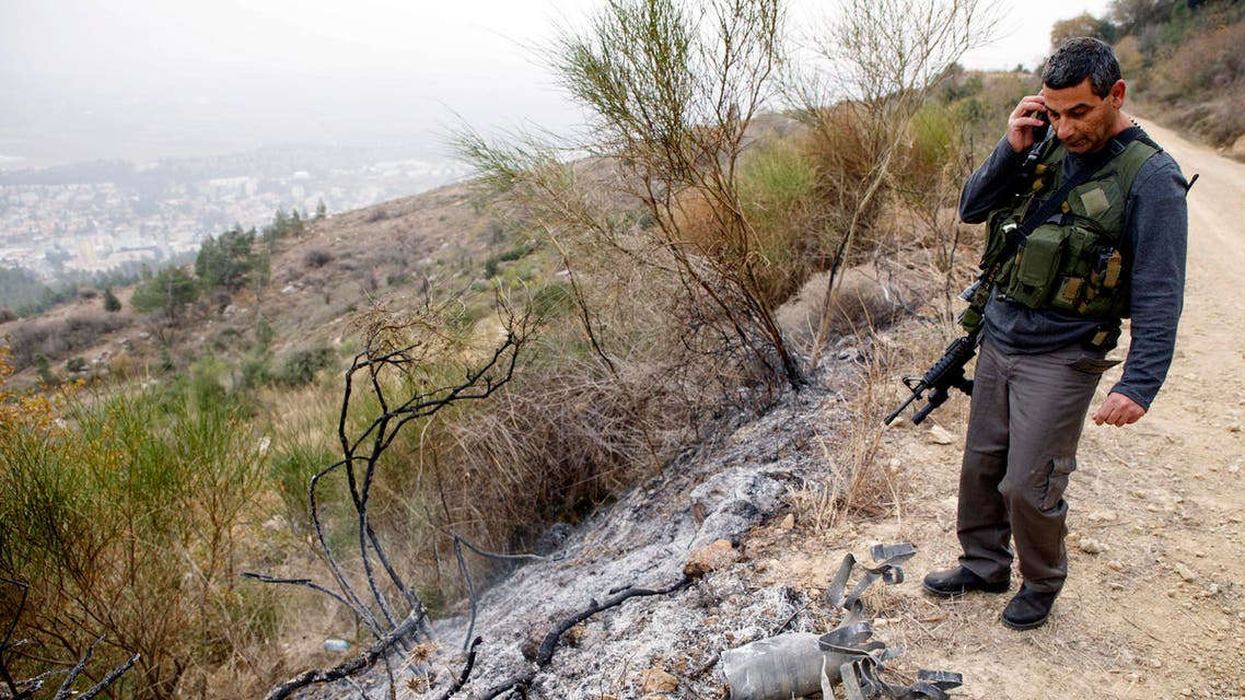 An Israeli security coordinator stands next to the remains of a rocket after it landed near the northern town of Kiryat Shmona December 29, 2013.