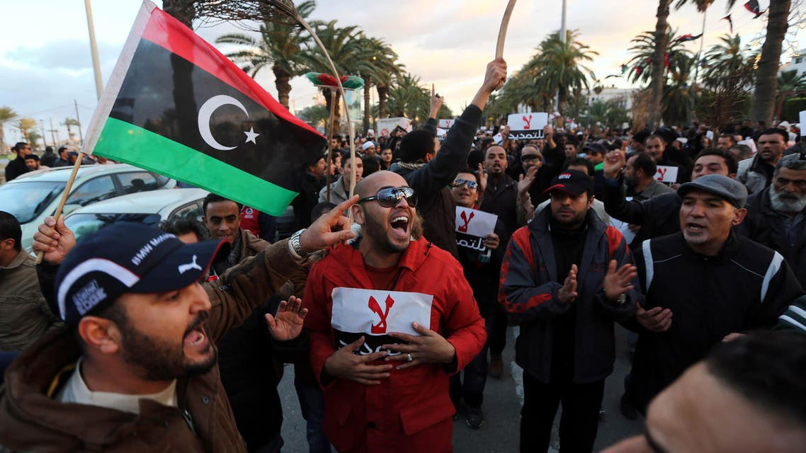 Libyan protestors hold placards as they demonstrate against the extended mandate of the General National Congress, the country's highest political authority, in Tripoli's Martyr square, on December 27, 2013. (AFP)