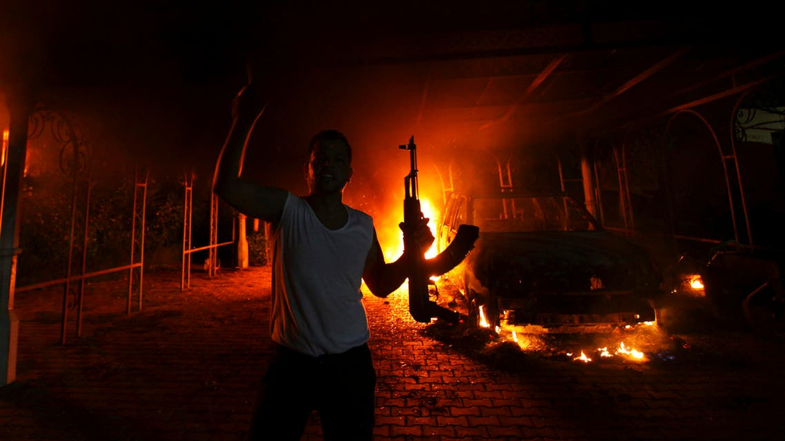 A protester reacts as the U.S. Consulate in Benghazi is seen in flames during a protest by an armed group said to have been protesting a film being produced in the United States September 11, 2012. reuters