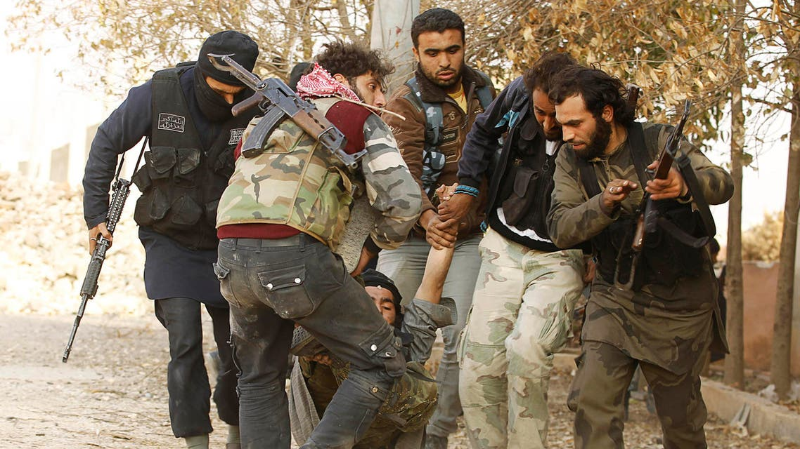 Free Syrian Army fighters carry a fellow fighter who was wounded during clashes with forces loyal to Syria's President Bashar al-Assad near Base 80 near Aleppo International airport, November 8, 2013
