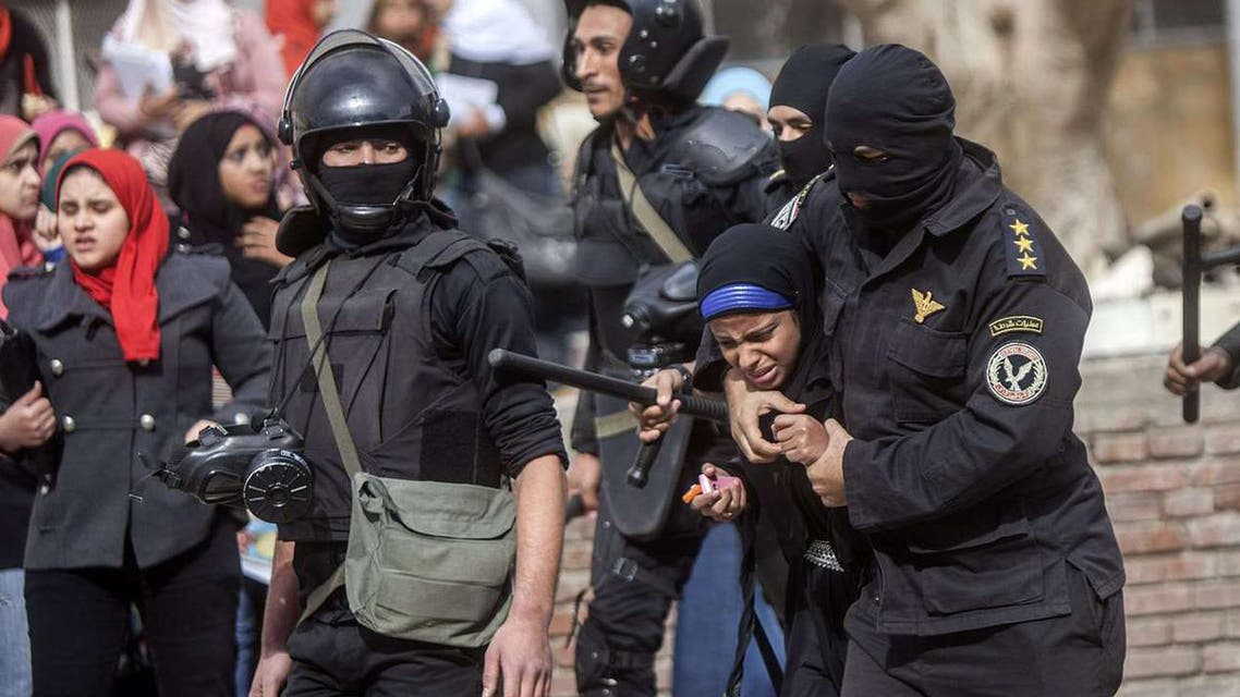 An Egyptian riot policeman detains a female student of al-Azhar University during a protest by students who support the Muslim Brotherhood inside their campus in Cairo on Dec, 30, 2013. (AFP)