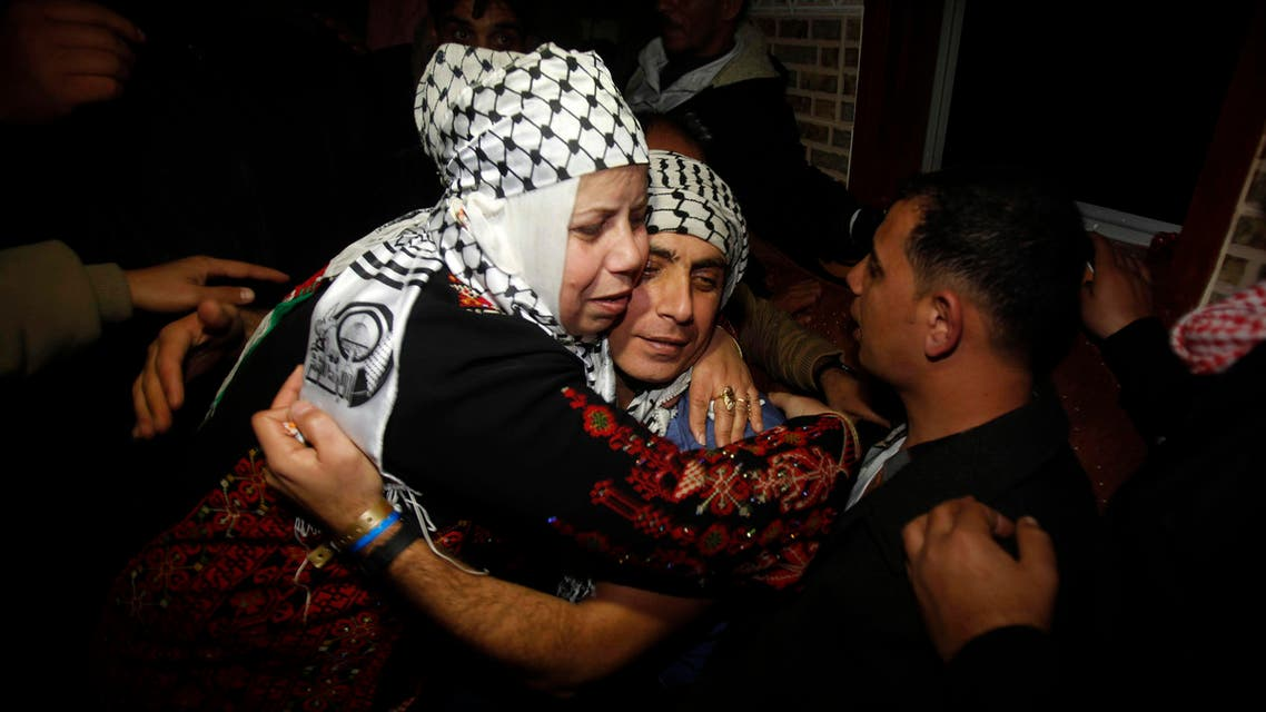 Freed Palestinian prisoner Rami Barbakh (C), who was held by Israel for 20 years, is hugged by his mother upon his release, in Khan Younis in the southern Gaza Strip December 31, 2013.