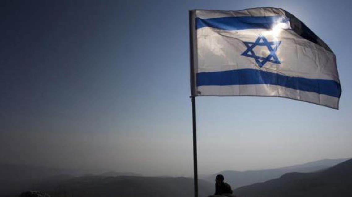 An Israeli soldier stands guard under an Israeli national flag during a tour made by Israeli parliament members in the Jordan Valley near the Jewish settlement of Maale Efrayim January 2, 2014.