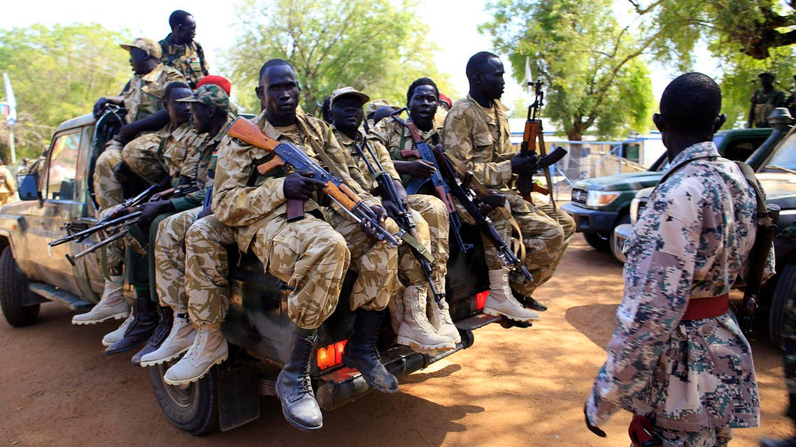 South Sudan army soldiers hold their weapons as they ride on a truck in Bor, reu
