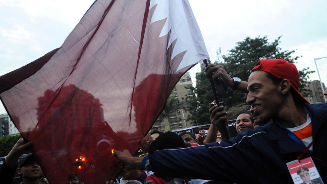 Egyptians burn a Qatari flag during a protest against what they say is Qatar's backing of ousted Egyptian president Mohamed Mursi's government, outside the Qatari Embassy in Cairo November 30, 2013