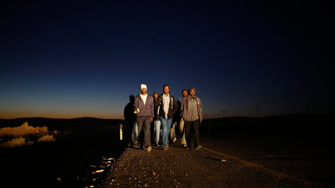 African migrants walk on a road after abandoning a detention facility in the southern Israeli desert December 15, 2013.