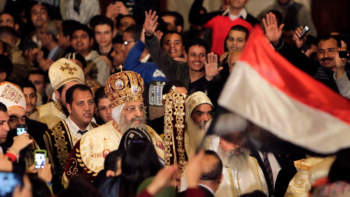 Egyptian Coptic Christians wave to Pope Tawadros II, the 118th Pope of the Coptic Orthodox Church of Alexandria and Patriarch of the See of St. Mark Cathedral, as they attend the Coptic Christmas Eve Mass in Cairo January 6, 2014.