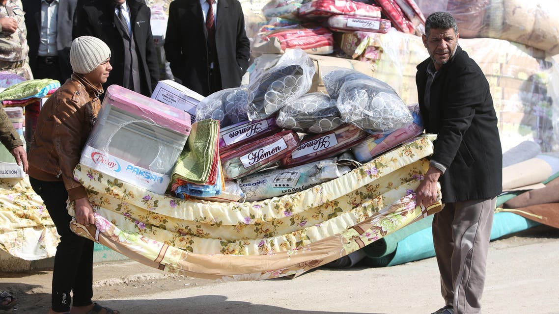 Sunni Muslim Iraqis who fled Fallujah with their families carry blankets and mattresses distributed by the International Organization for Migration (IOM) NGO in Ayn al-Tamer in Karbala province. (File photo: AFP)