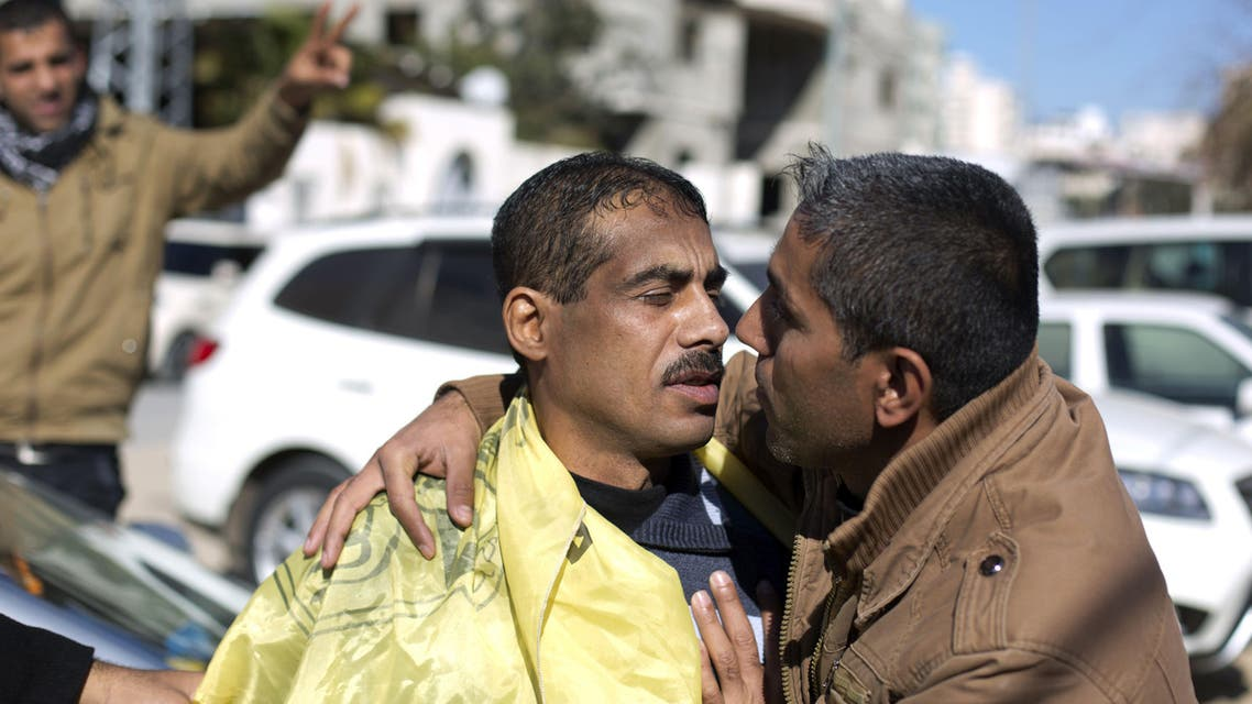 A Palestinian man (L) is hugged by a relative after he was freed from a Hamas-run jail in Gaza City, on January 8, 2014. (AFP)