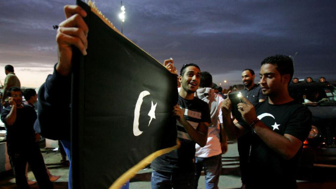 Libyan protesters hold the flag of the eastern Cyrenaica region during a demonstration calling for greater autonomy in the eastern city of Benghazi