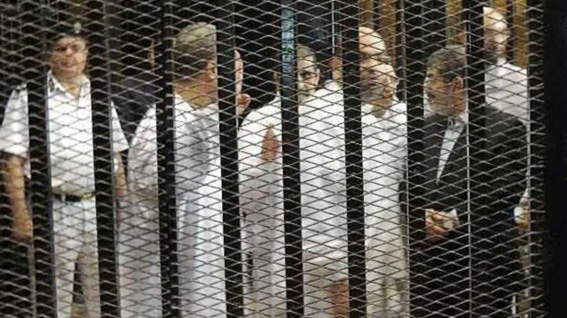 Ousted former Egyptian president Mohamed Mursi (R) speaks with other senior figures of the Muslim Brotherhood in a cage in a courthouse on the first day of his trial, in Cairo, November 4, 2013. (Reuters)