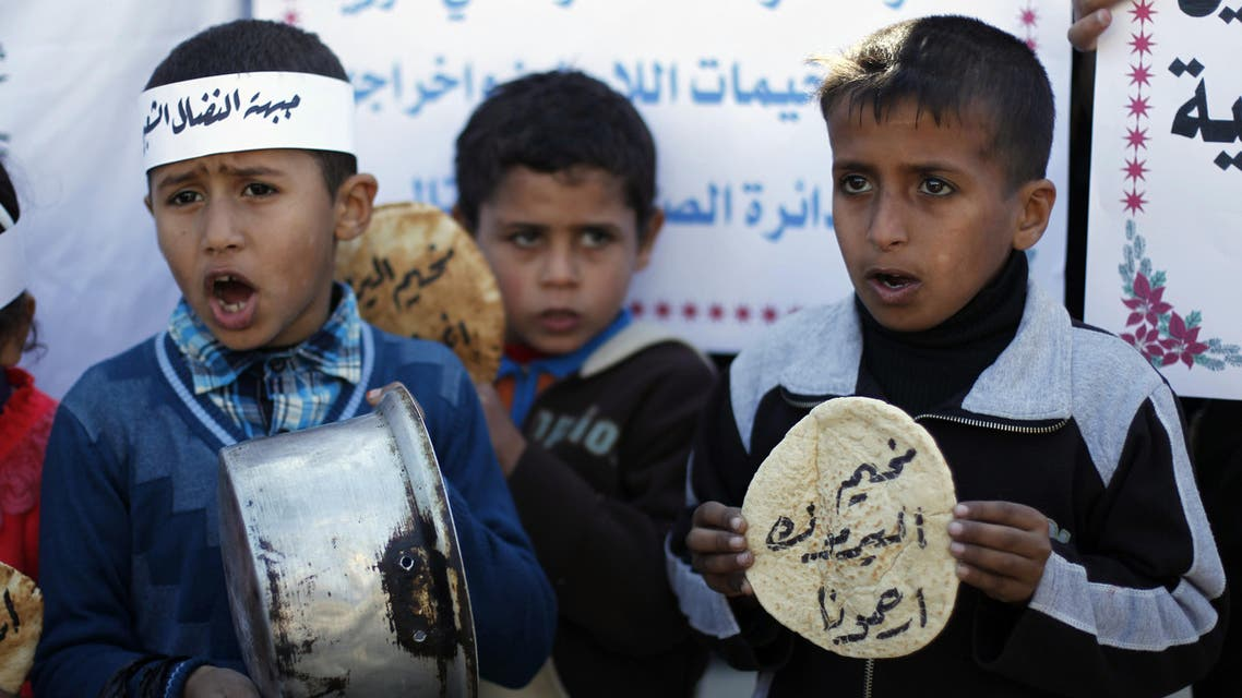 Palestinians children holds bread and pots on January 8, 2014, as they take part in a protest against the poor living conditions at the Yarmuk refugee camp in the Syrian capital Damascus, on January 8, 2014, in Rafah town in the southern Gaza Strip. (AFP)
