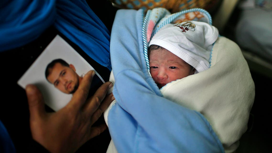 Palestinian baby boy Al-Hassan, the son of Palestinian prisoner Tamer al-Za'anin (seen in photograph) who was conceived with al-Za'anin's sperm smuggled out of an Israeli prison, is held by his grandmother after he was born in a hospital in Gaza City January 10, 2014. reuters
