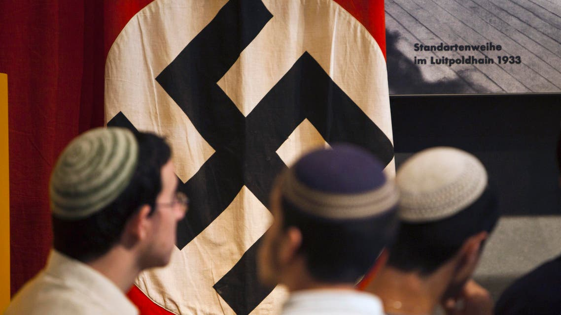 Visitors stand in front of a flag with the Nazi swastika at Yad Vashem's Holocaust History Museum in Jerusalem April 18, 2012.