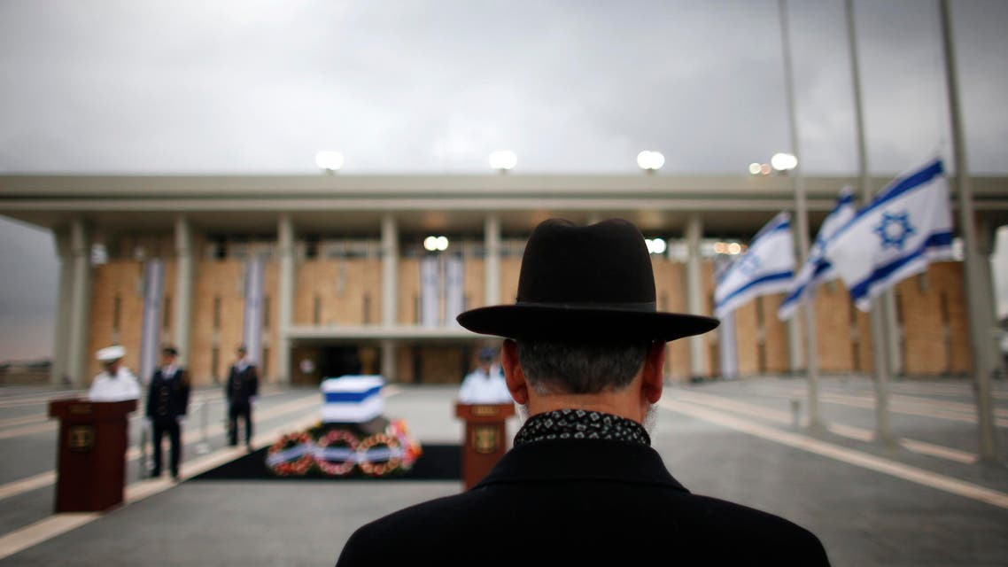 A man stands in front of the flag draped coffin of former Israeli Prime Minister Ariel Sharon outside the Knesset in Jerusalem January 12, 2014. reuters