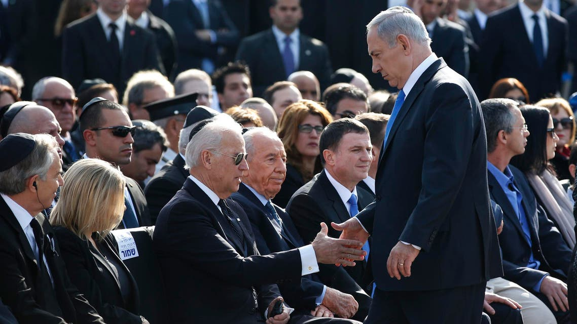 Israel's Prime Minister Benjamin Netanyahu (standing) shakes hands with U.S. Vice President Joe Biden during a memorial ceremony for the former Israeli prime minister Ariel Sharon at the Knesset, Israel's parliament, in Jerusalem January 13, 2014.