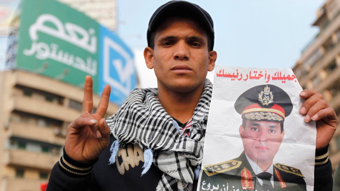 A supporter of Egypt's army chief and defense minister General Abdel Fattah al-Sisi holds a poster with Sisi's image during a protest in support of the new constitution at Tahrir Square in Cairo December 20, 2013. reuters