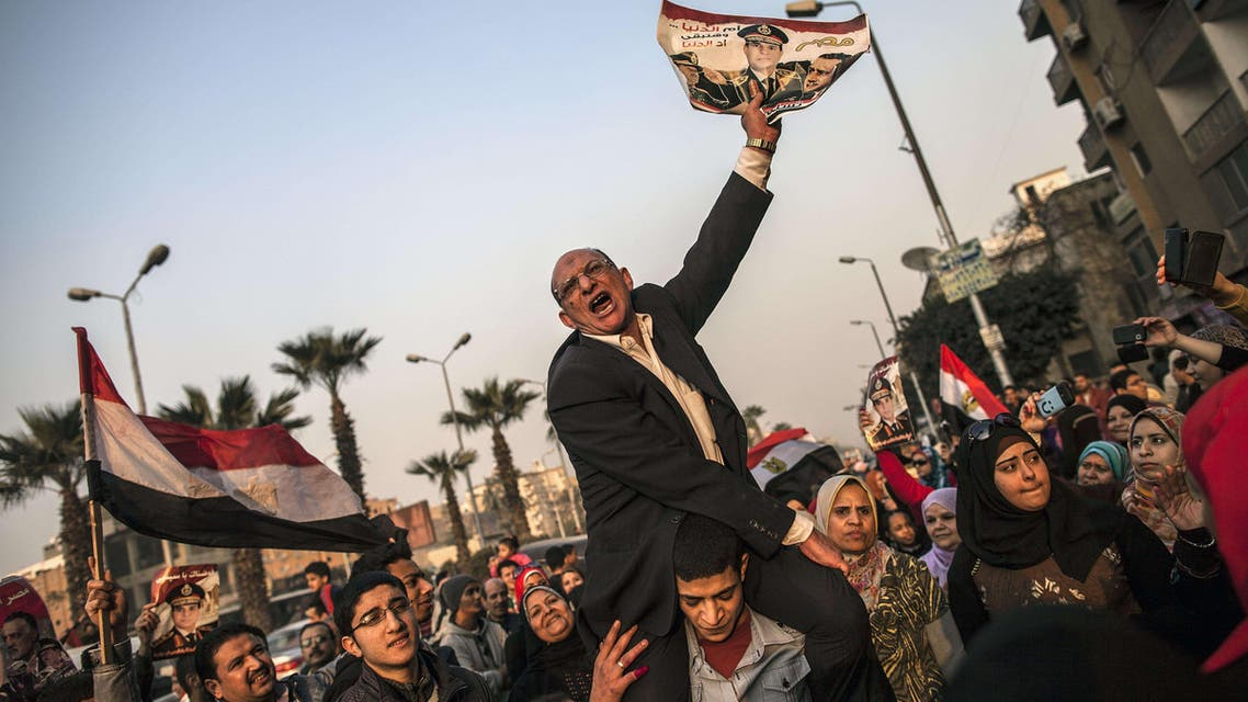 An Egyptian man holds a portrait of Egypt's Defence Minister General Abdel Fattah al-Sisi outside a polling station during the vote on a new constitution on January 14, 2014 in Giza, Cairo AFP