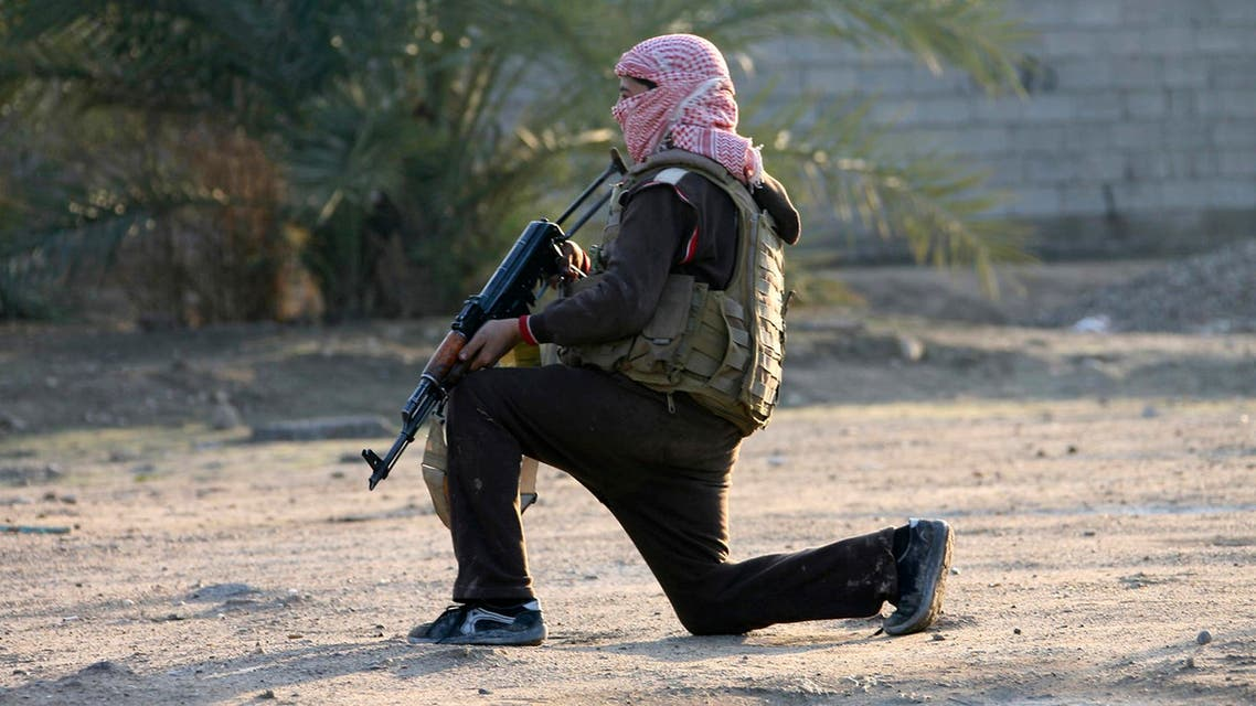 A masked Sunni Muslim gunman takes position with his weapon during a patrol in the city of Falluja, 70 km (44 miles) west of Baghdad January 15, 2014. reuters
