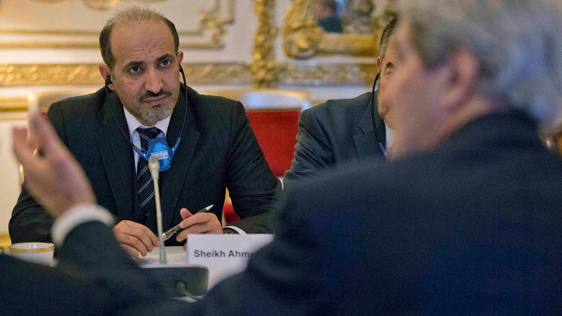 Syrian National Coalition Chief Ahmad al-Jarba (L) listens to U.S. Secretary of State John Kerry during the start of their meeting at the U.S. Ambassador residence in Paris January 13, 2014.