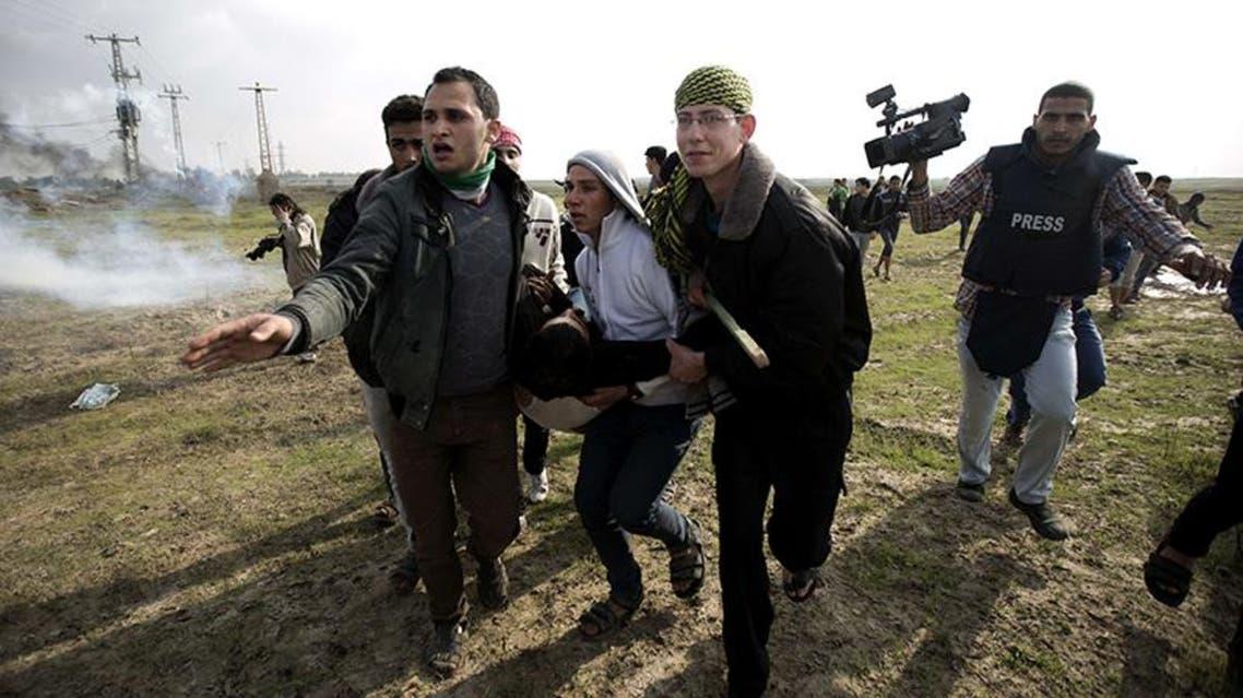 نقل جريح فلسطيني اصيب برصاص الجيش الاسرائيلي اثناء مظاهرة بالقرب من السياج الفاصل مع غزة