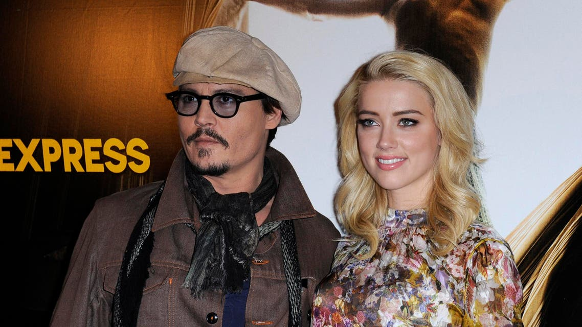 """U.S. actors Johnny Depp (L) and Amber Heard pose for photographers during a photocall for the film """"The Rum Diary"""" in Paris Nov.  8, 2011. (Reuters)"""