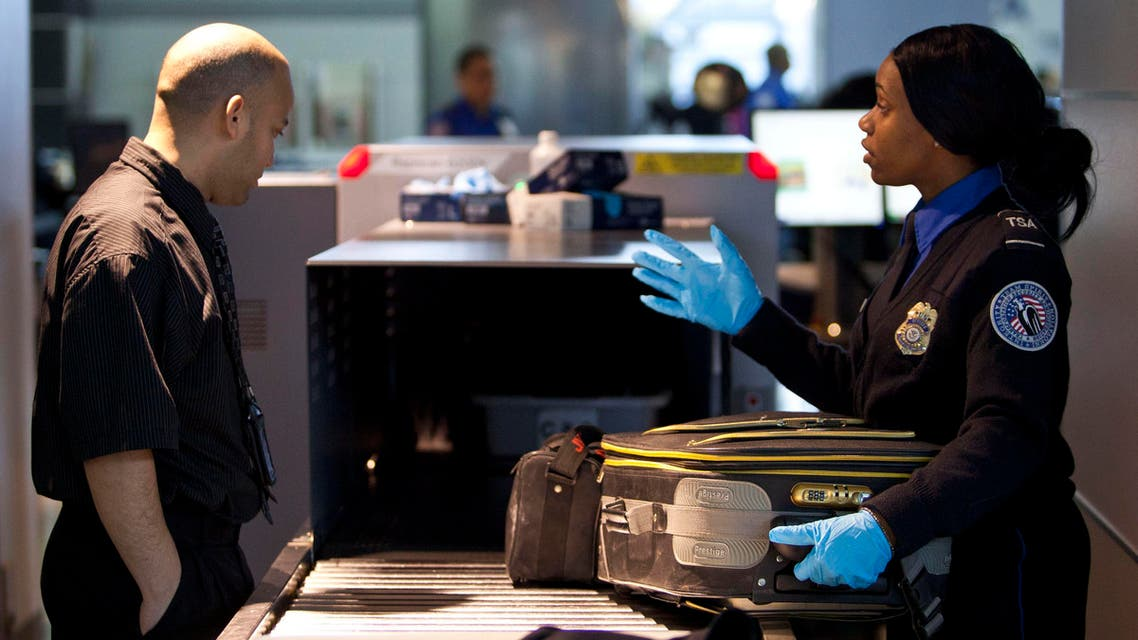 A Transportation Security Administration (TSA) security agent takes a traveler's luggage for a second security check at John F. Kennedy Airport in New York, Feb. 29, 2012. (Reuters)