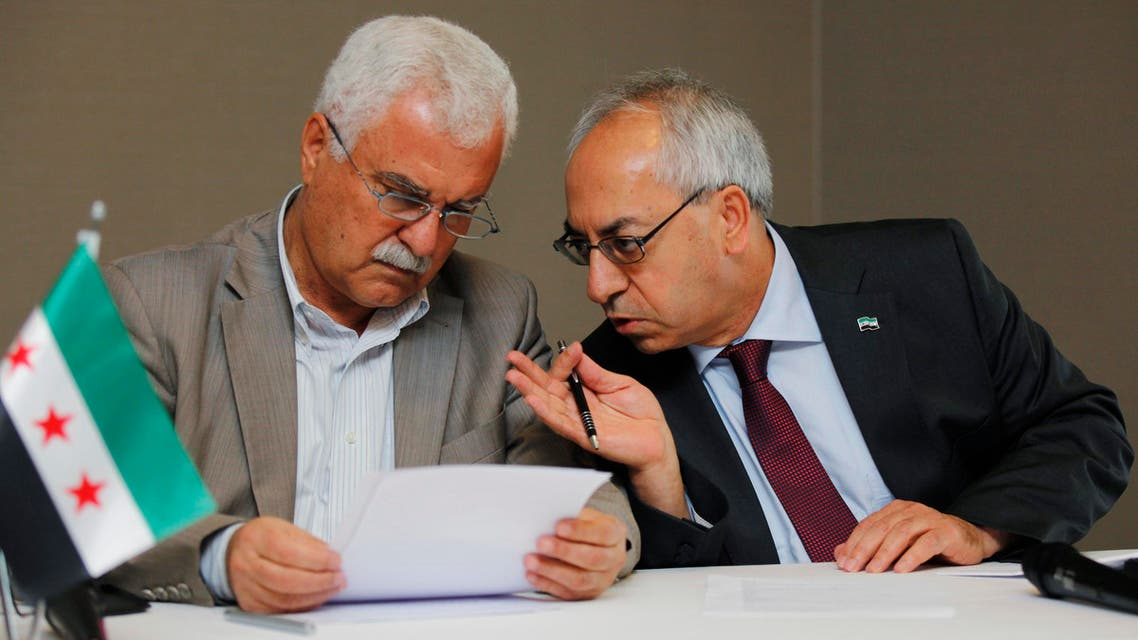 Abdelbasset Sida, leader of the opposition Syrian National Council (R), chats with council member George Sabra