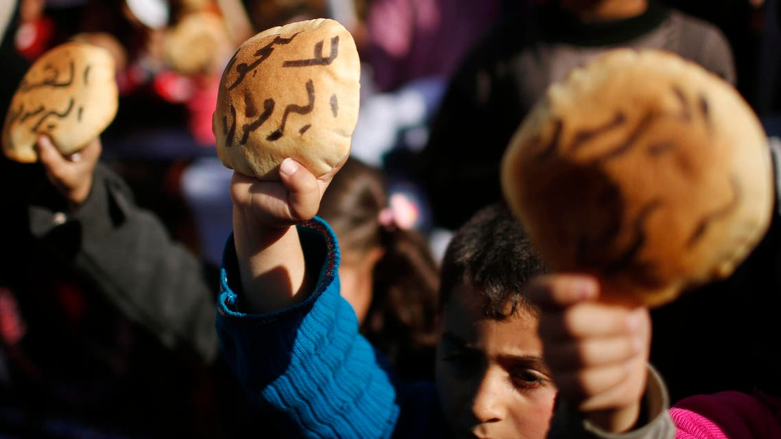 Palestinian children hold bread as they take part in a rally to show solidarity with Palestinian refugees in Syria's main refugee camp Yarmouk, in Gaza City Jan. 16, 2014. (Reuters)