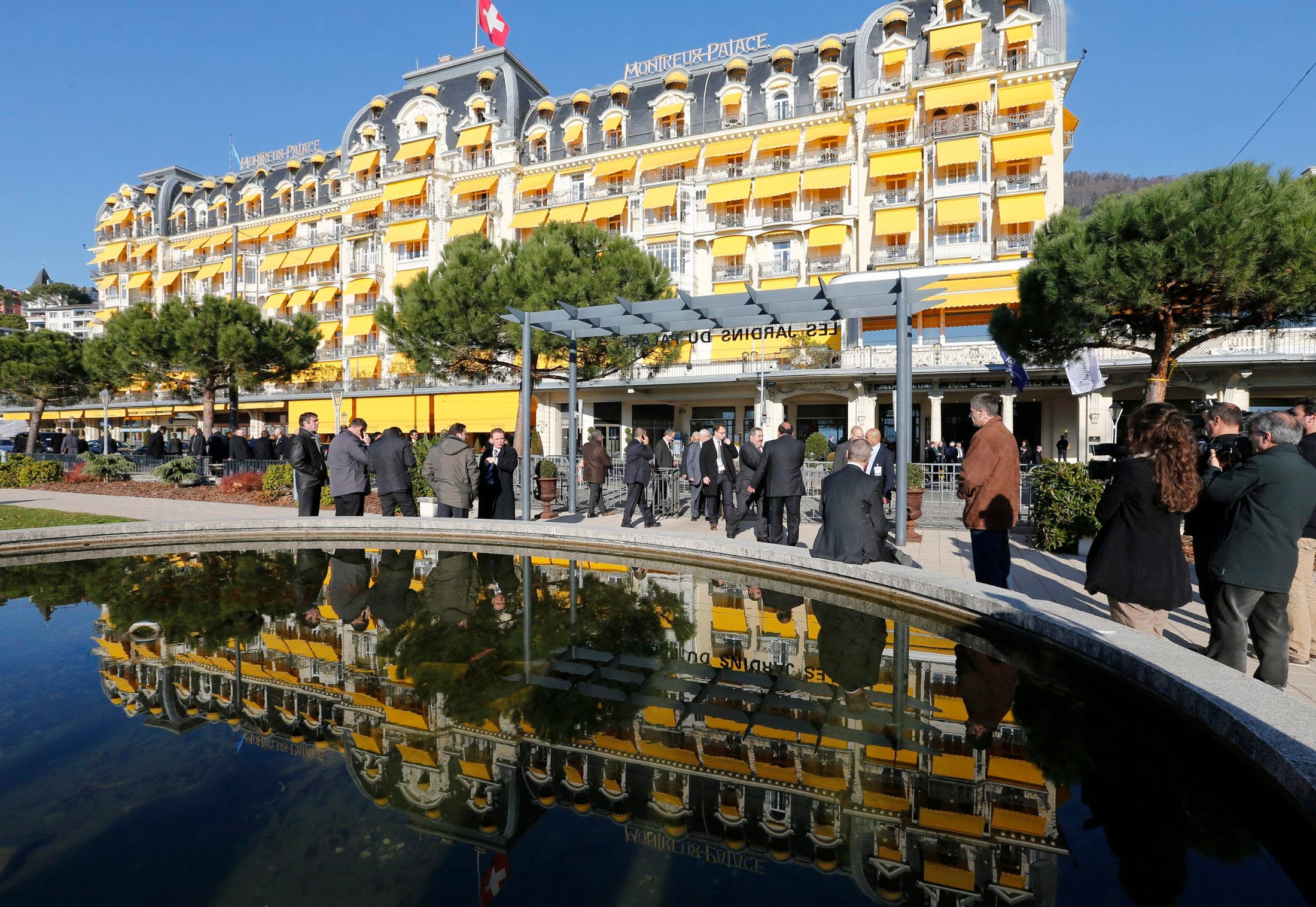 The Montreux Palace hotel facade is reflected in a pool as security officials rest during the second session of Geneva-2 peace conference in Montreux Jan. 22, 2014. (Reuters)