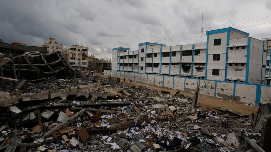 Palestinians walk past a destroyed building and a school, which witnesses said was damaged in an Israeli air strike, in Gaza City November 24, 2012.