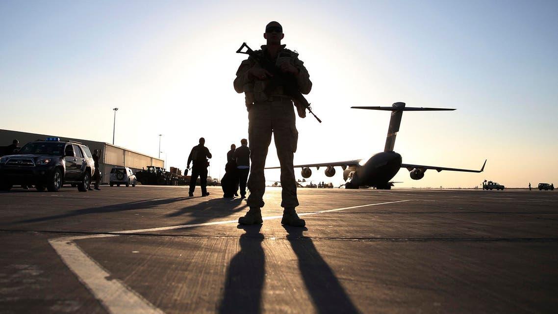 A U.S. soldier stands guard near a C-17 Globemaster III aircraft sitting on the tarmac at Kandahar Air Base Dec. 8, 2013. (Reuters)