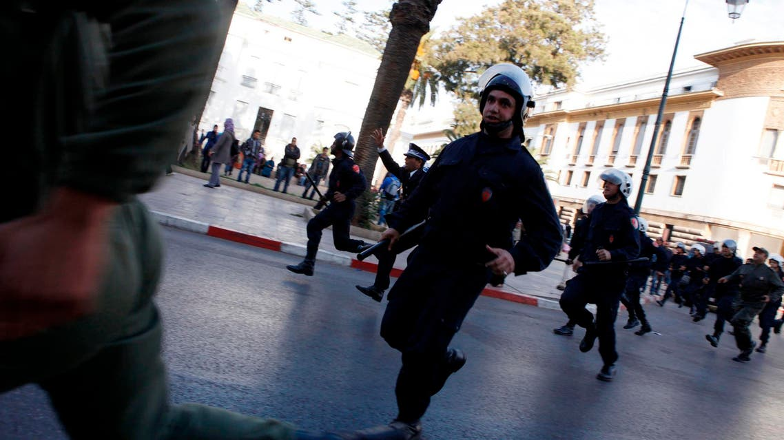 Police officers run after unemployed graduates who were marching in solidarity with anti-government protesters in the north, in Rabat March 14, 2012. reuters