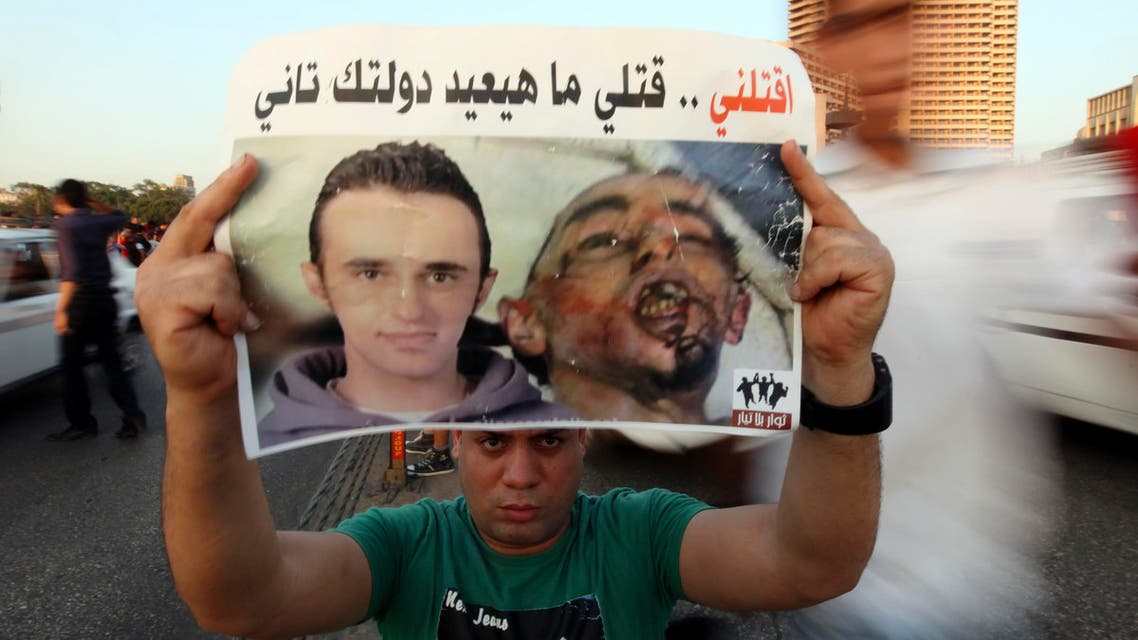 A demonstrator carries a poster of Egyptian Khaled Said on the second anniversary of his death over Qasr El Nile bridge in Cairo