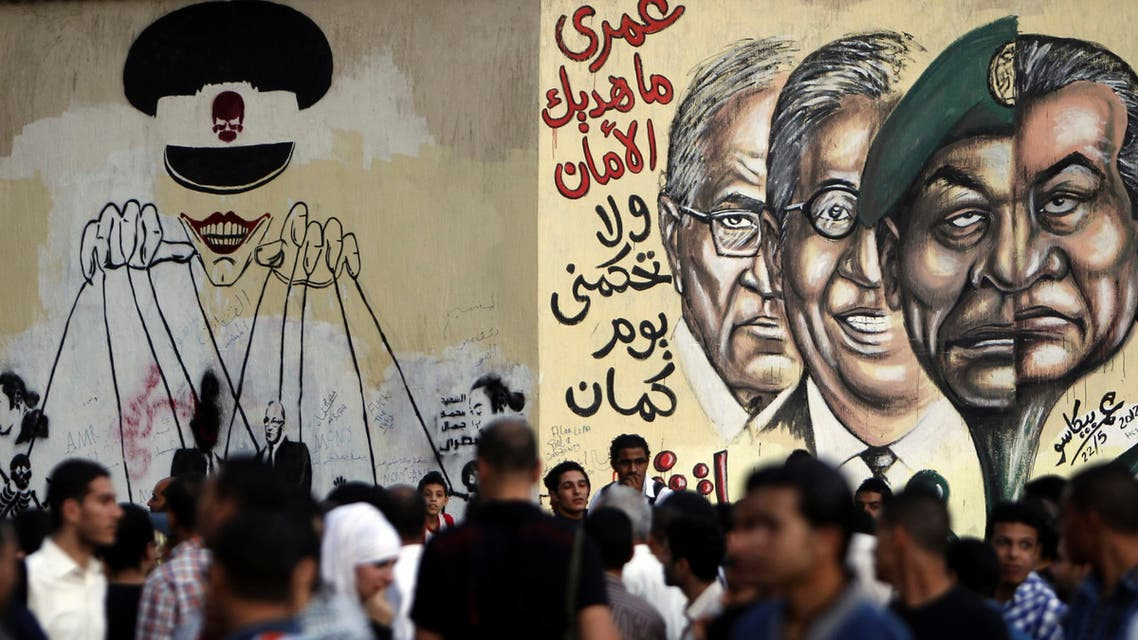People walk in front of a wall sprayed with graffiti, depicting the ruling military council controlling the presidential elections as a puppet show in 2012. (Reuters)