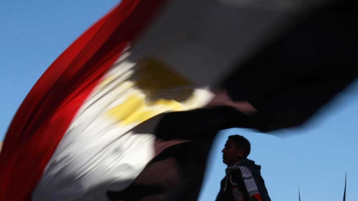 A demonstrator carries an Egyptian flag near Tahrir square where demonstrators are gathering to mark the first anniversary of Egypt's uprising, January 25, 2012.