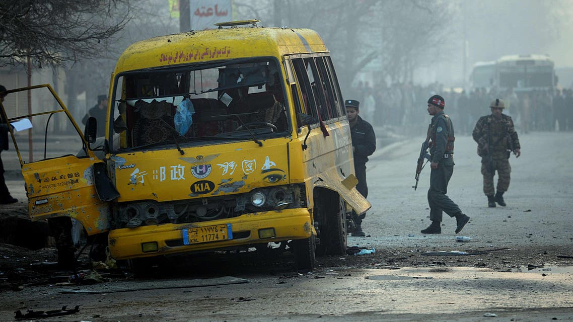Afghan investigators inspect a damaged bus at the site of a suicide attack in Kabul on January 26, 2014.