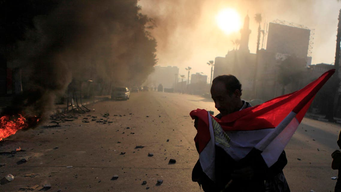 Anti-government protester holds a national flag during clashes at Ramsis street, which leads to Tahrir Square in downtown Cairo, on the third anniversary of Egypt's uprising, January 25, 2014. (Reuters)