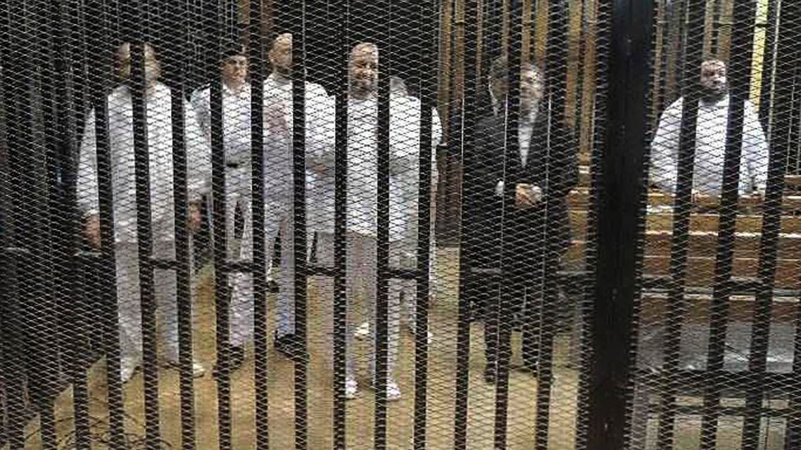 Ousted former Egyptian president Mohamed Mursi (2nd R) stands with other senior figures of the Muslim Brotherhood in a cage in a courthouse on the first day of his trial, in Cairo, November 4, 2013.