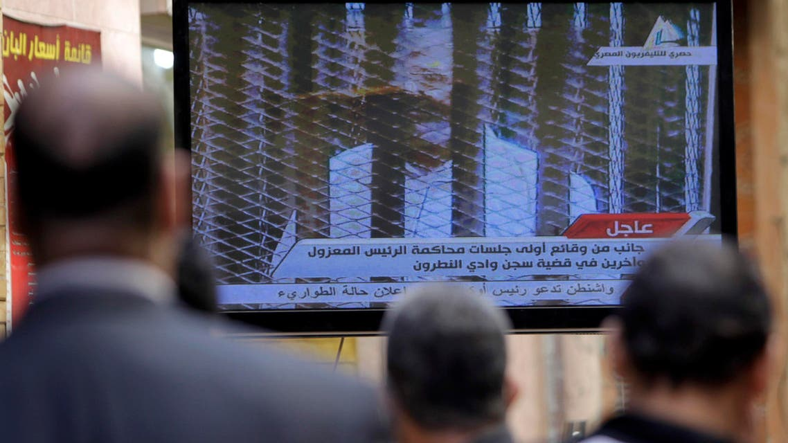Egyptians watch television showing the trial of ousted Egyptian president Mohamed Mursi, in Cairo January 28, 2014.