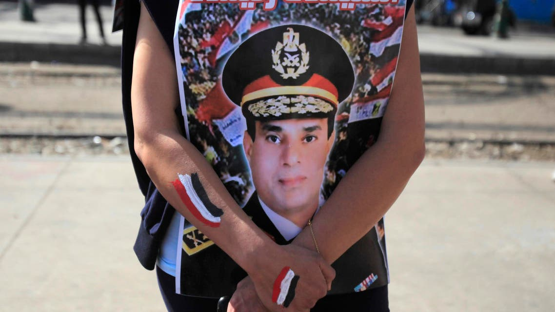 A supporter of Egypt's army chief General Abdel Fatah al-Sisi hugs his poster during celebrations of the third anniversary of Egypt's uprising, in front of El-Thadiya presidential palace in Cairo January 25, 2014.