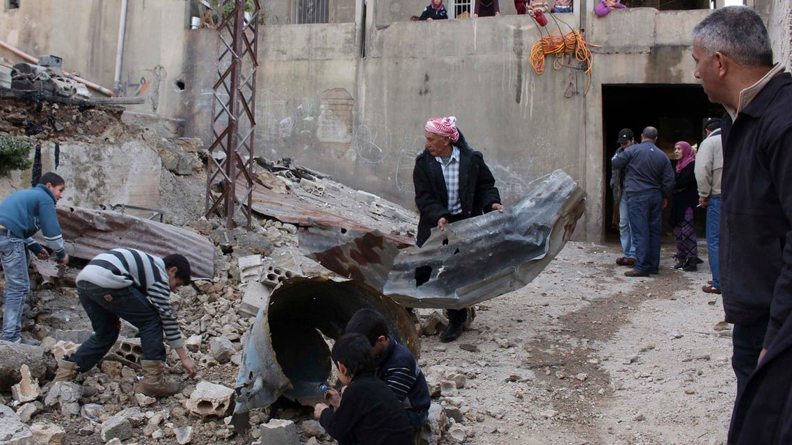 Residents inspect a site hit by shelling fired from Syria into the Lebanese village of Mashta Hammoud in Akkar January 31, 2014.