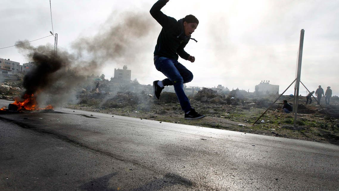 A Palestinian protester jumps as tyres burn in the background during clashes with Israeli soldiers in Jalazoun refugee camp near the West Bank city of Ramallah January 31, 2014.