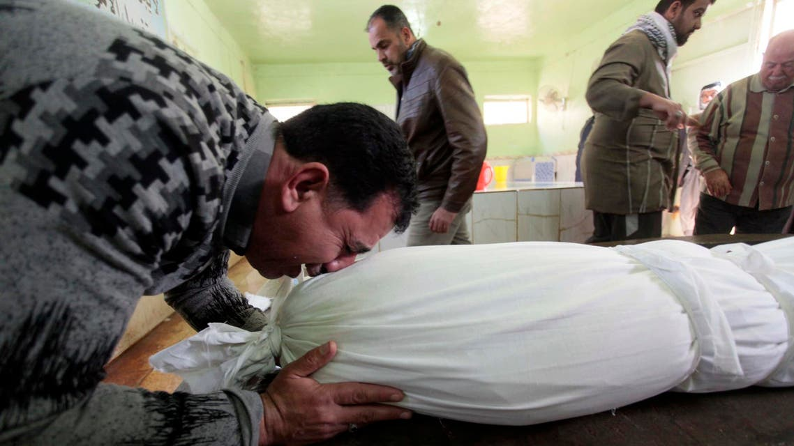 A man reacts near the shrouded body of his son, who was killed by a car bomb attack, before his burial at a cemetery in Najaf, 160 km (100 miles) south of Baghdad Jan. 31, 2014. (Reuters)