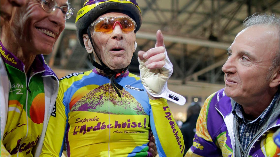 French cyclist Robert Marchand (C), aged 102, reacts with Gerard Mistler (L), President of the Ardechoise Cycling Club, after he covered 26.98 kms in one hour at the indoor Velodrome National in Montigny-les-Bretonneux, southwest of Paris January 31, 2014.